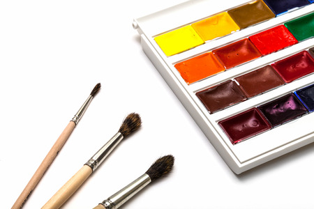 Set of watercolors with three brushes isolated on white background. photo