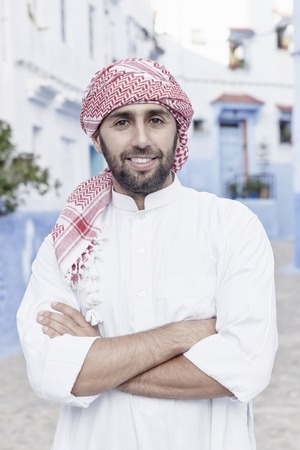 traditional clothes: Young smiling handsome arabic man wearing traditional clothes