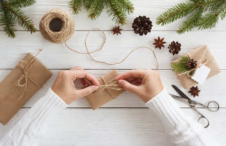 Preparation christmas gifts on a white wooden table with fir branches Stock Photo