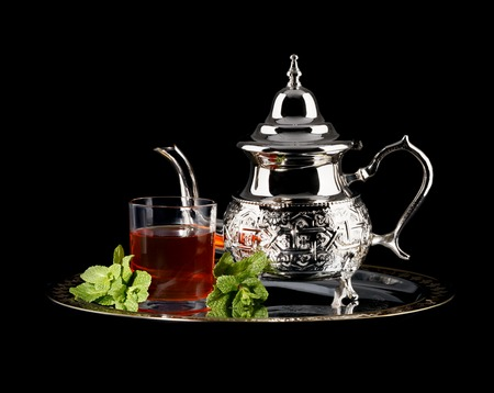 Traditional moroccan teapot with glass of green tea isolated on black background
