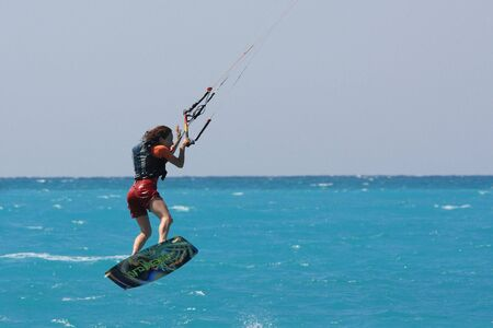 towed: kite boarder flying through the air on a sunny day