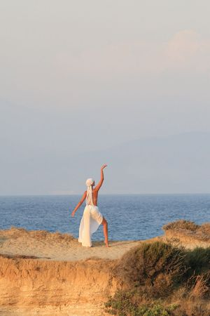 full strenght: Woman meditating at sunset in Greece Stock Photo