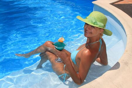 Woman enjoying a fresh cocktail in a blue pool in Greece Stock Photo