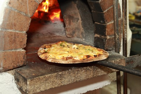 Gourmet Pizza coming out of wood fired Pizza Oven in restaurant Stock Photo
