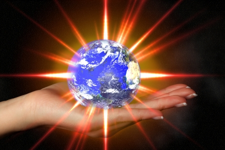 hands fire passion: Womans hand holding an exploding earth - global warming Stock Photo