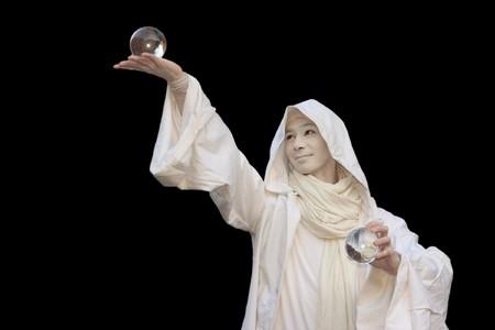 manipulating: White Wizard manipulating Crystal balls isolated on black background.