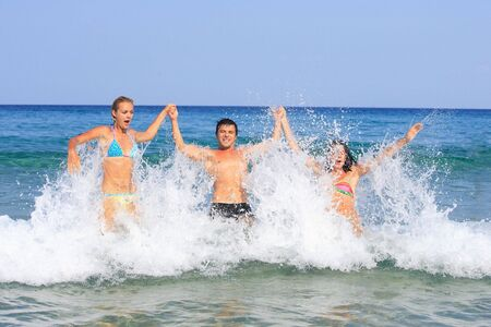 aegean sea: Portrait of joyful group of people having fun in the sea and laughing