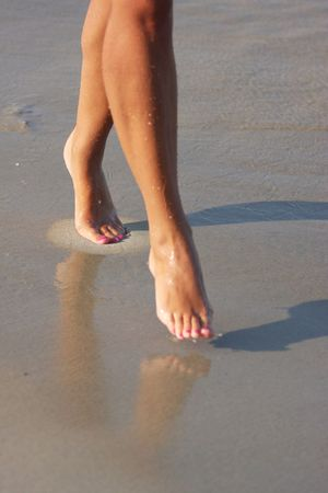 bare women: nice legs of a pretty girl walking in water
