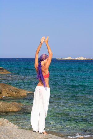 Beautiful girl meditating on the beach in Greece Stock Photo - 5417045