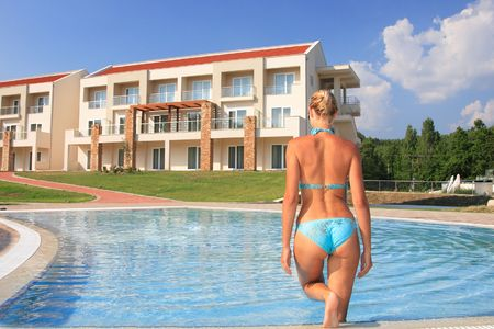 woman from behind: Pretty blonde woman enjoying a swimming pool in Greece