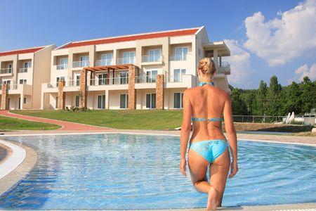 bikini butt: Pretty blonde woman enjoying a swimming pool in Greece