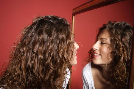miror: A beautiful sexy women  looking at her reflection in the miror on red background   Stock Photo