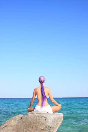 Young beautiful tanned woman in bikini meditating by the sea in Greece