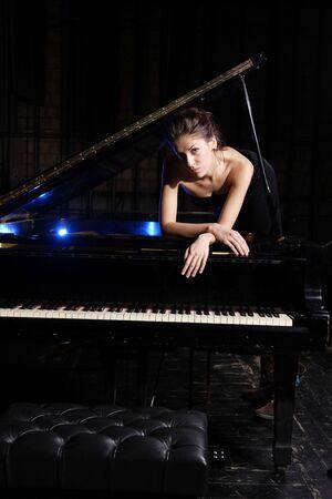 piano player: A beautiful young woman playing piano
