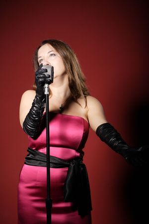 A sexy singer with a vintage microphone on red background   photo