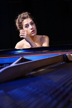 A beautiful young woman playing piano   photo