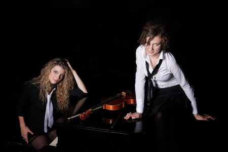Two beautiful young sexy women posing with violon and piano photo