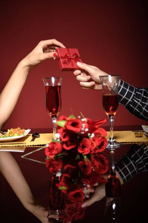 Close up of young couple at restaurant table holding hands   photo