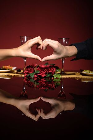 Close up of young couple at restaurant table making a heart with theyr hands   photo