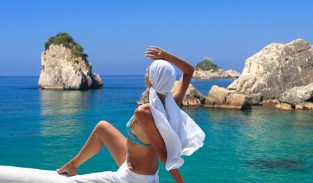 womna: Beautiful young womna relaxing by the beach in Greece