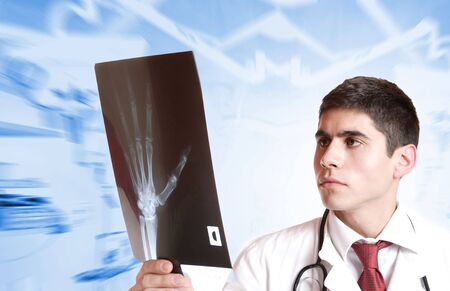 Caucasian mid adult male doctor holding up xrays.