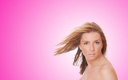 A beautiful young woman with her hair blowing in front of a pink background   photo