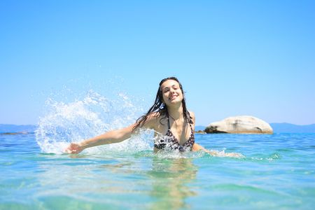 Happy young woman in sea with open hands.     photo