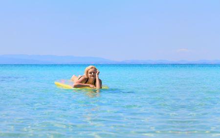 matress: beautiful young woman in bikini on a matress in the sea
