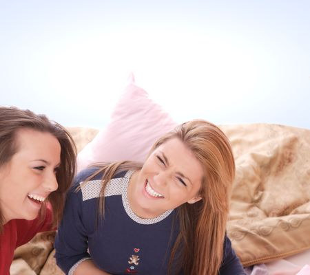 Two beautiful young woman fighting with pillows in bed   photo