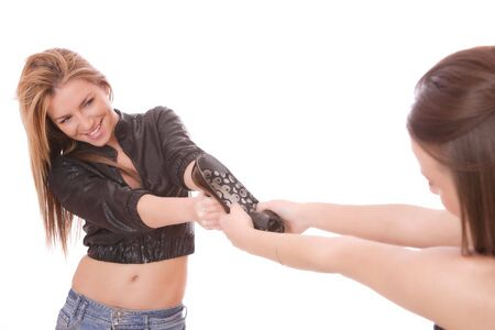 Two young woman fighting for a shoe over a white background     photo