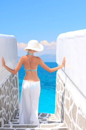 Beautiful young woman relaxing by the beach in Greece Standard-Bild