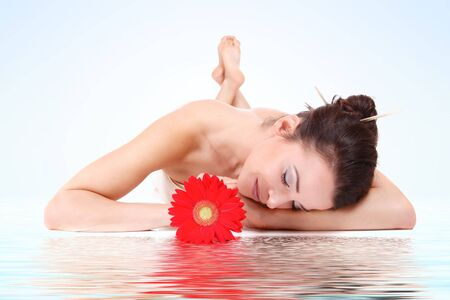 Attractive woman with flower getting spa treatment photo