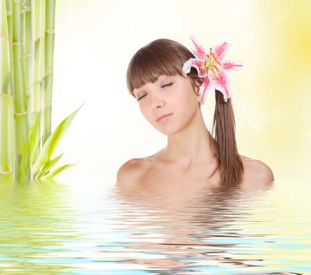 Young beautiful woman with bamboo and reflection in water  photo