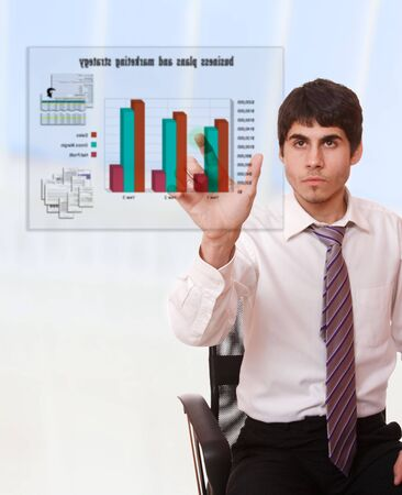 Young businessman studying a business plan on a virtual screen Stock Photo - 6312151