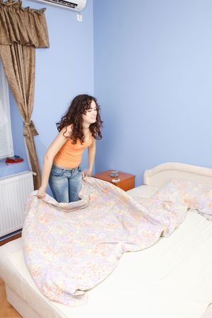 A teen girl happily making her bed in her room. Stock Photo - 6312105
