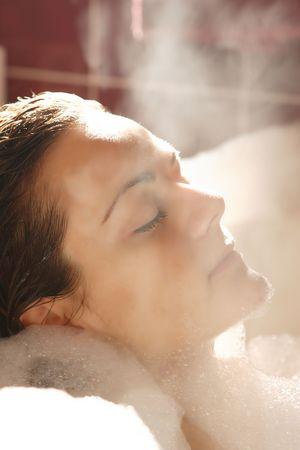 Young woman enjoys bath-foam in the bathtub.