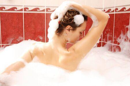 bath women: Young woman enjoys bath-foam in the bathtub.