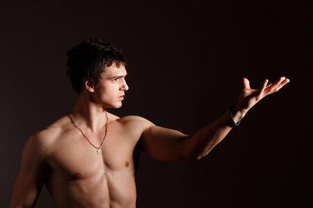 Studio portrait of handsome man showing his muscles