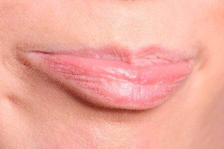 Young womans glossy pink lips close up   photo