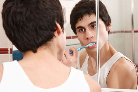 Reflection in a bathroom mirror of a young man brushing his teeth Stock Photo - 6553139