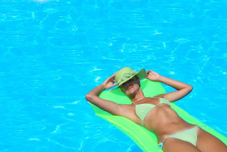 Beautiful young woman relaxing in a swimming pool in Greece  Banque d'images