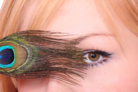 Closeup of a beautiful woman with peacock feather eye   photo