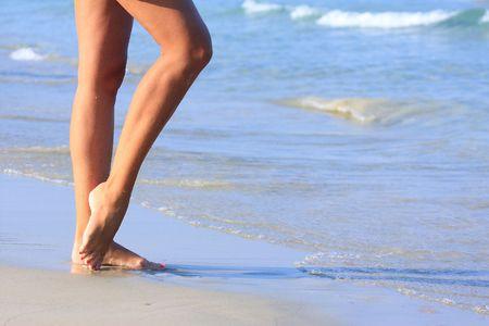 nice legs of a pretty girl walking in water  Standard-Bild