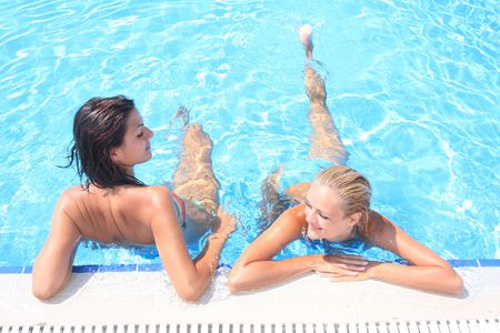 Two girlfriends  enjoying the sun in a swimming pool while  on vacation  Banque d'images