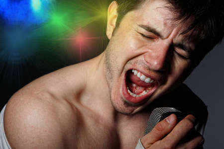 Young Man Singing over dark background