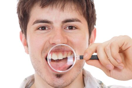 Man examining his teeth with magnifier photo