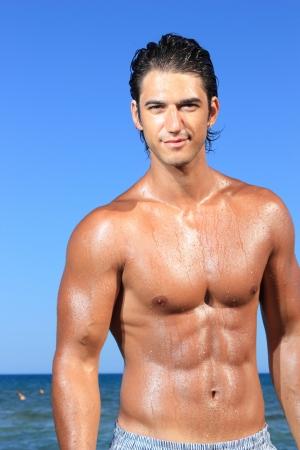 torso nudo: sexy caucasica adatta uomo posa in una spiaggia