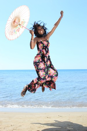 Beautiful African-American model with umbrella by the sea photo