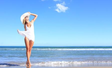 Junge Frau stehend auf einem Strand und die Sonne genie�en  Lizenzfreie Bilder