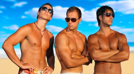 fit man: Three Young Men Relaxing On the Beach Stock Photo